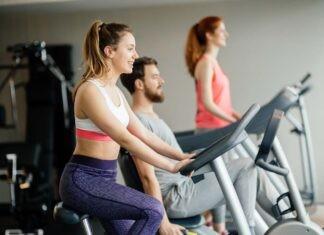 Menschen trainieren auf Heimtrainer, Crosstrainer und Rudergerät